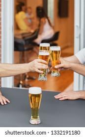 Cropped image Hands of a group of voiced glasses of beer, parties and celebrations. beer glasses at home on the terrace of the house