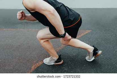 Cropped image of hands tying shoelaces on sneaker, running surface background. Hands of sportsman with pedometer tying shoelaces on sporty sneaker. Running equipment concept.