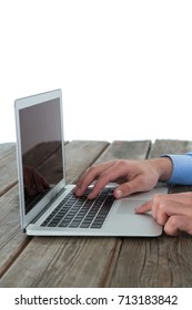 Cropped image of hands using laptop at table against white background