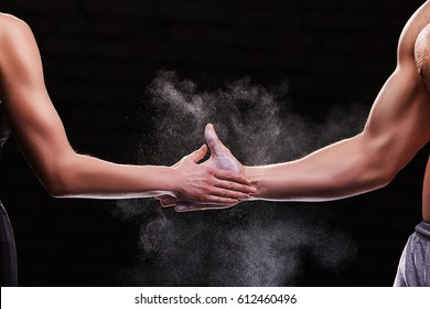 Cropped image of hands of a young couple on dark background. Crossfit fitness, bodybuilding concept