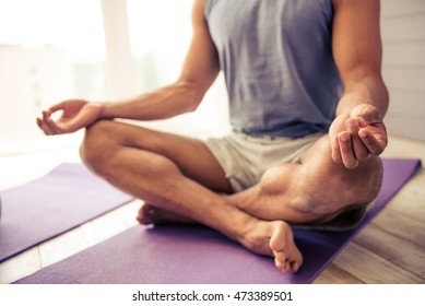 Cropped image of handsome Afro American man in sports clothes meditating in lotus position on mat while doing yoga at home