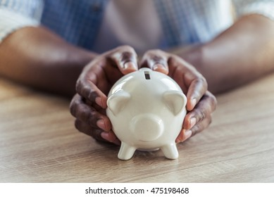 Cropped image of handsome Afro American businessman holding a piggy bank