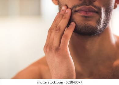 Cropped image of handsome Afro American man touching his face