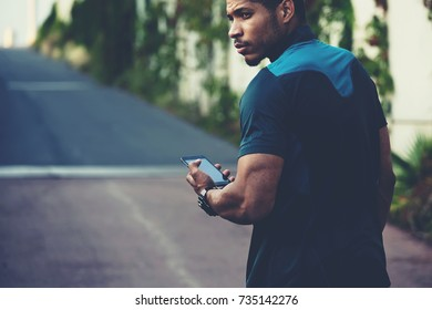 Cropped image of handsome afro american male runner holding cellphone in hands, Application for training