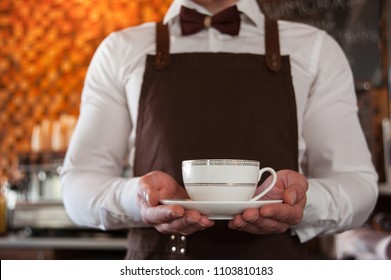 Cropped image of handsome barista in apron holding a cup of coffee at the bar counter in cafe. Cup in focus