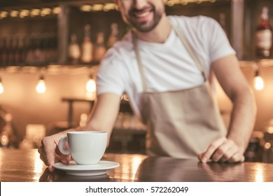 Cropped image of handsome barista in apron holding a cup of coffee and smiling while working at the bar counter in cafe. Cup in focus