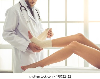 Cropped image of handsome doctor bandaging woman's injured leg while working in his office