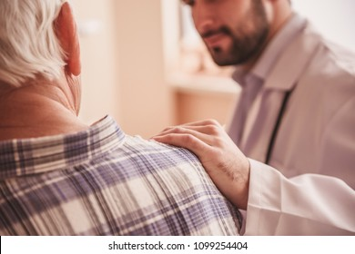 Cropped image of handsome doctor talking with an old man, holding hand on his shoulder and smiling while sitting in hospital ward
