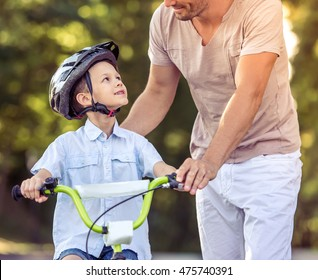 Cropped image of handsome father teaching his cute little son riding bike in park. Both are smiling