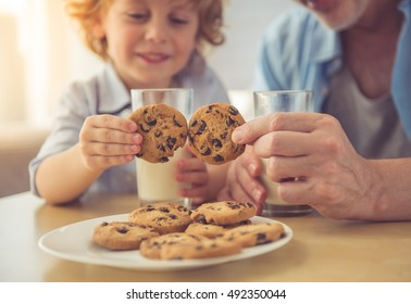 Cropped image of handsome grandpa and grandson drinking milk and eating cookies together at home