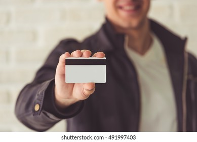 Cropped image of handsome guy holding a credit card and smiling. Card in focus