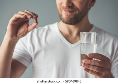 Cropped image of handsome man is holding a pill and a glass of water, on gray background