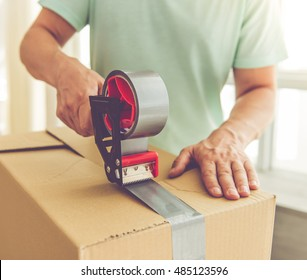 Cropped image of handsome mature man in casual clothes packing his stuff into the boxes using an adhesive tape while moving to the new apartment
