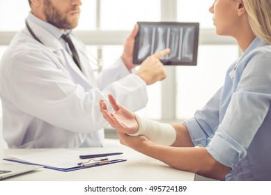 Cropped image of handsome medical doctor talking to female patient with damaged hand and showing her a X-ray picture on tablet while working in his office