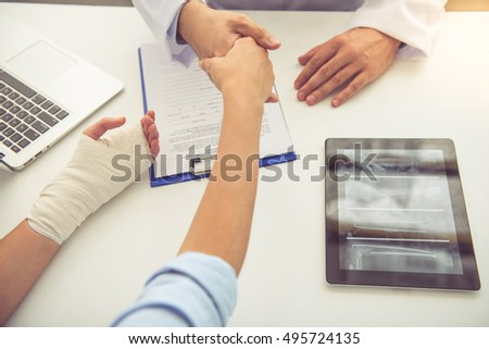 Cropped image of handsome medical doctor shaking hands with female patient while working in his office