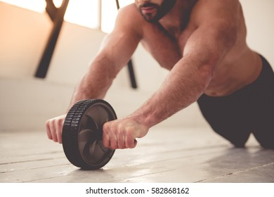 Cropped image of handsome muscular man with bare torso working out with exercise wheel