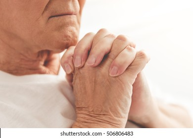 Cropped image of handsome old man holding hands together and praying while lying in bed