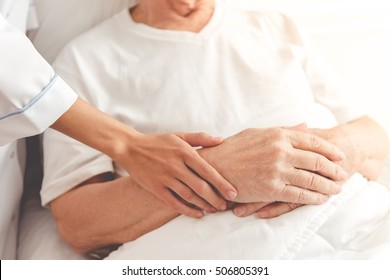 Cropped image of handsome old patient lying in bed in hospital. Doctor is holding man's hand