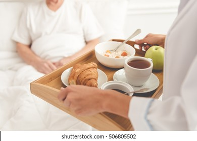 Cropped image of handsome old patient getting his meal from nurse while lying in bed in hospital