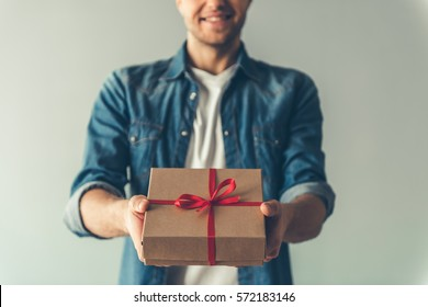 Cropped image of handsome romantic guy smiling while holding a present for his couple, on gray background