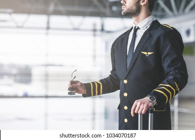 Cropped image of handsome young male pilot in the airport terminal.