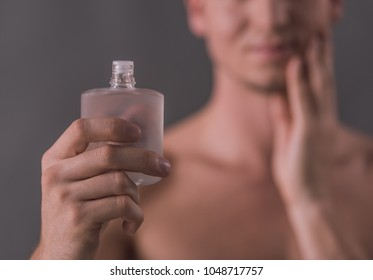 Cropped image of handsome young man holding aftershave lotion, on gray background