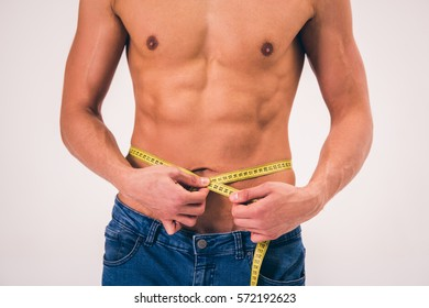 Cropped image of handsome young man measuring his waist using a tape measure, on gray background