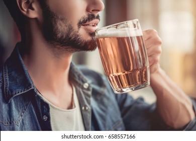 Cropped image of handsome young man is drinking beer in bar