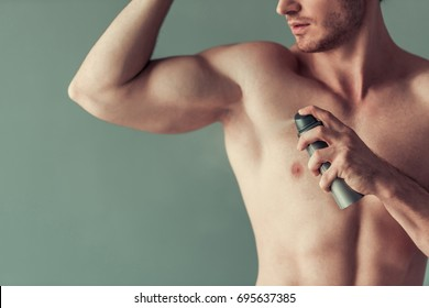 Cropped image of handsome young man with bare torso using a spray deodorant, on gray background