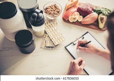 Cropped image of handsome young sportsman making notes while preparing sport nutrition in kitchen at home - Shutterstock ID 617836010