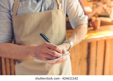 Cropped image of handsome young waiter making notes while taking an order, standing in the cafe
