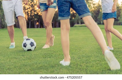 Cropped image of happy family playing soccer in park
