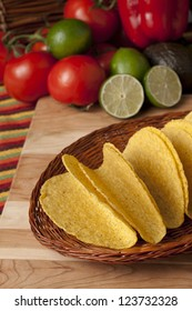 Cropped image of hard taco shells and vegetables on the background