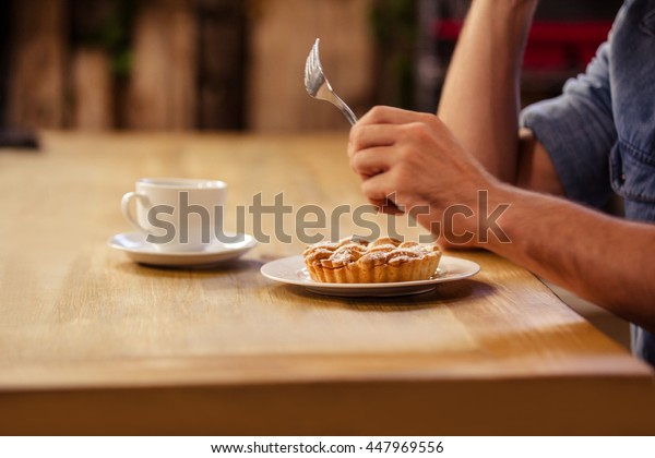 Cropped image of hipster man eating and drinking coffee at cafe