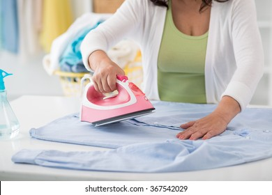 Cropped image of housekeeper steaming clothes