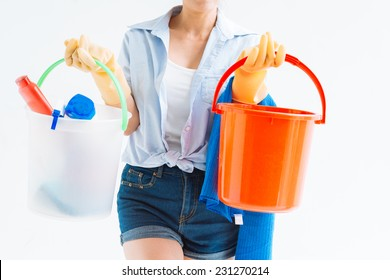 Cropped image of housewife holding buckets with detergents