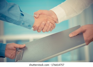 Cropped image of human handshaking after signing a contract on the foreground