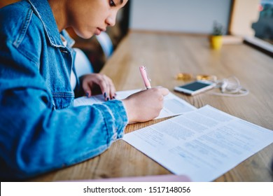 Cropped image of intelligence female student making notes on papers from course work and correcting false with pen, clever hipster girl preparing to university exam while sitting in cafeteria