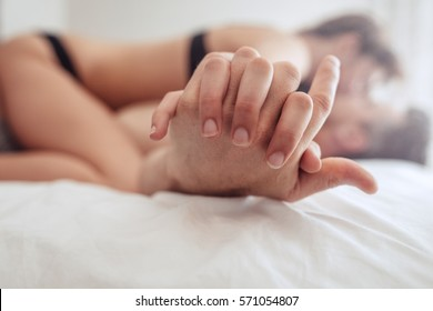 Cropped image of intimate couple holding hands while having sex on bed.