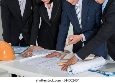Cropped image of investors analyzing construction plan of building