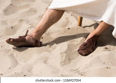 c1a31e8c47e2c4 cropped image of Jesus in robe and sandals sitting on sun lounger in desert