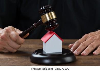 Cropped image of judge holding gavel on house model at desk