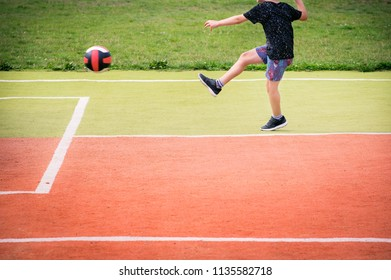 Cropped image of little boy kicking ball on the school sport field.