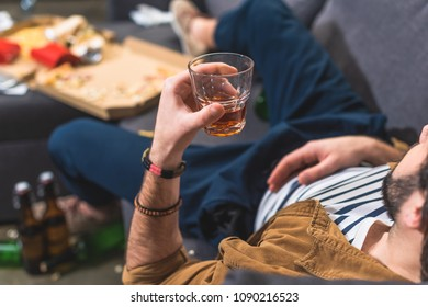 cropped image loner lying on sofa with glass of whiskey at living room