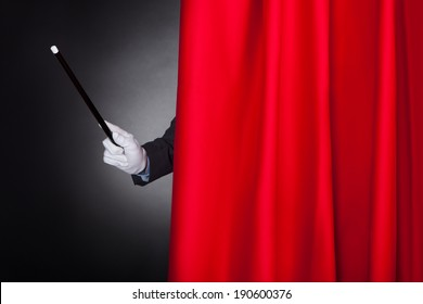 Cropped image of magician holding wand behind stage curtain
