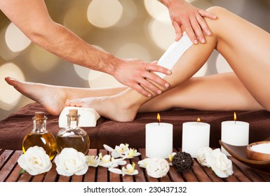 Cropped image of male beautician waxing woman's leg in spa