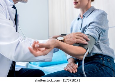 cropped image of male doctor measuring pressure of female patient by tonometer in hospital room