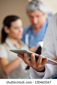 Cropped image of male doctor using digital tablet with colleagues in background
