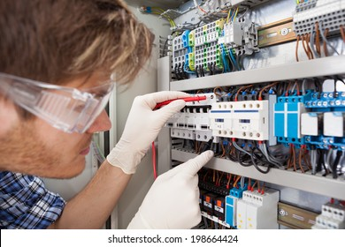 Cropped image of male electrical engineer examining fusebox with multimeter probe