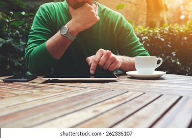 Cropped image male freelancer sitting at the table with cup of coffee, digital tablet and smart phone, man's hands typing message on touch screen tablet while sitting on balcony terrace, flare sun